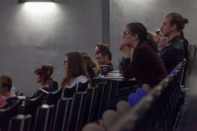 People sitting in auditorium listen intently
