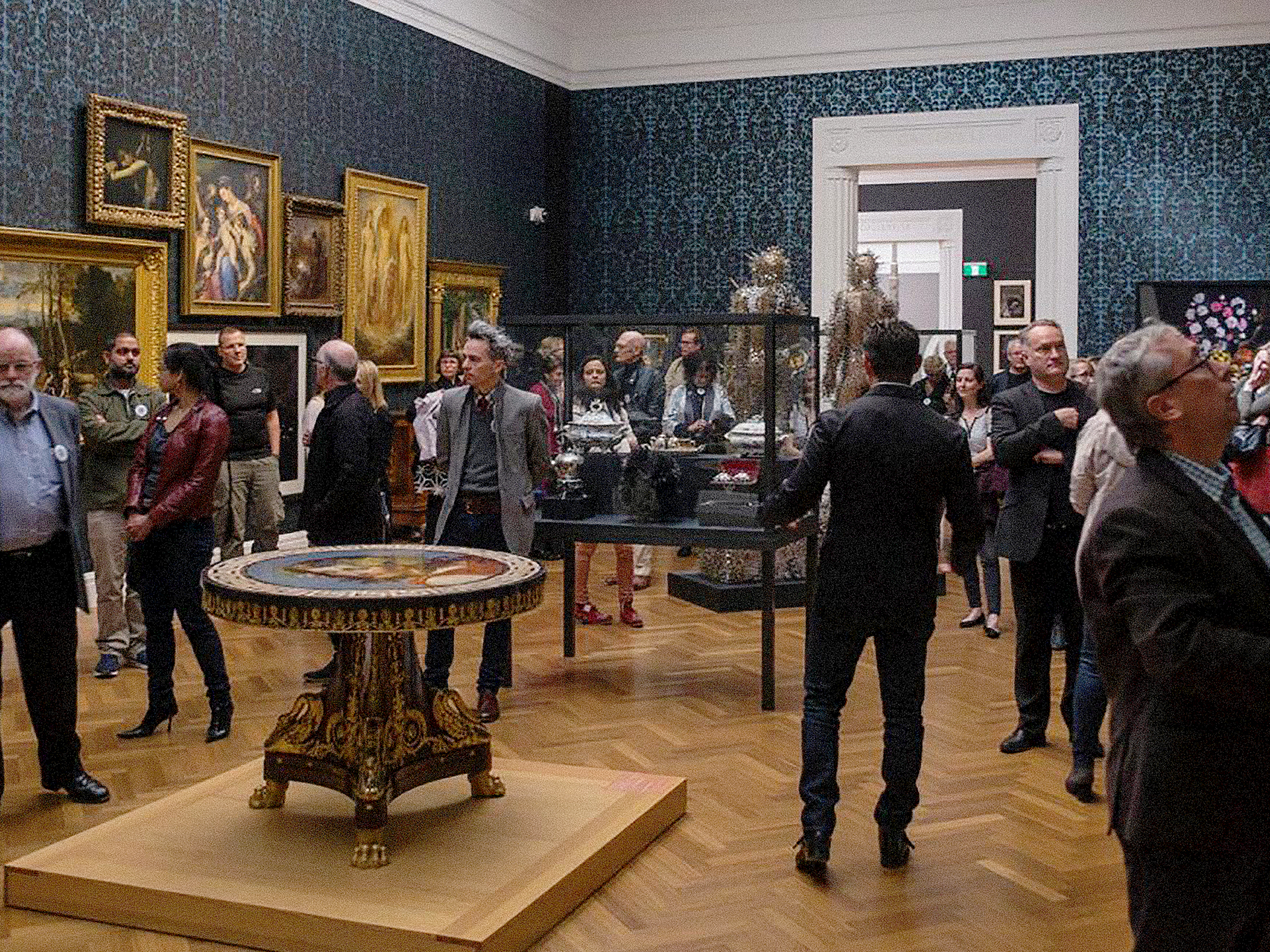 Many well dressed people exploring a museum