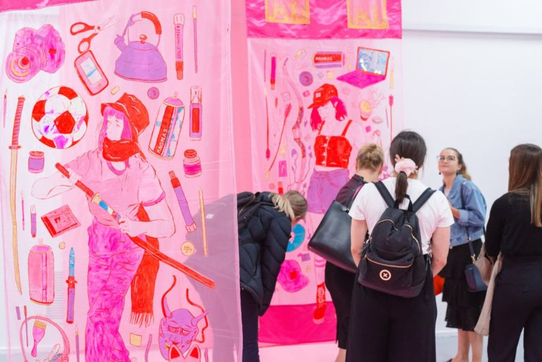 Group of women looking at a pink work of art in gallery