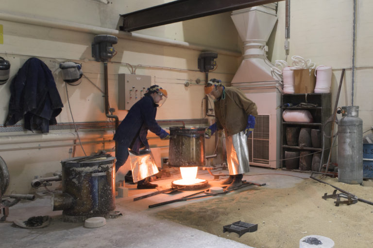 Two people in protective equipment hold large metal pot over flame
